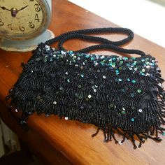 20's Inspired Gatsby Fringe Evening Bag Pretty and tiny 1920's beaded flapper bags were highly decorated to match the beautiful dresses of the era. Small enough to carry makeup compacts, a few dollars, and cigarettes (gasp!) they were fashion accessories more than practical bags. This evening bag is inspired by the Roaring 20's with black beaded strap and black beading and sequin fringe. Bags