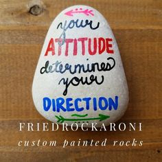 Your attitude determines your direction painted rock on natural white stone. Rock measures about 2 across (at the widest part) and about tall. This rock has a glossy, weatherproof sealant applied for indoor/outdoor decor. Rock Painting Ideas Easy, Rock Painting Designs, Paint Designs, Painted Rocks Craft, Hand Painted Rocks, Stone Crafts, Rock Crafts, Inspirational Rocks, Gifts For Hubby