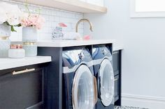 Laundry room inspiration with navy front loading washer and dryer. Laundry room has gold faucet and long gold pulls on the gray cabinetry.