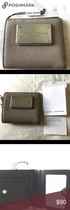 """Marc by Marc Jacobs Cement Classic Bifold Wallet This is a 100% authentic, brand new Marc Jacobs Bifold Wallet in the beautiful color of """"cement."""" It comes with the care instructions as this, like many other of Marc Jacobs products, are made of a gorgeous, soft leather.  **RETAILS: $130**  DETAILS: Pebbled exterior, snap button closure, silver-tone logo detail  Interior lining, credit card slots, bill pocket, transparent ID window 4"""" L x 3 1/2"""" H x 1 1/4"""" W Leather body, Polyurethane trim…"""