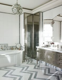 A London master bath features chevron-pattern inlaid marble floors and a crystal ceiling fixture.