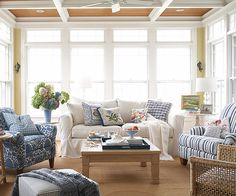 Serene Sunroom              Three walls of gorgeous transom-topped windows invite generous amounts of natural light and a delightful cross breeze in this sunroom. The room's color scheme was inspired by a seaside setting. Soothing colors of soft blues, pale yellows, sage greens, and warm whites create a serene, beachy backdrop