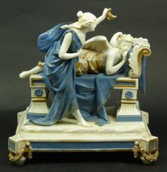 Antique Marchese Ginori Capodimonte Italian porcelain two figure group sculpture depicting Psyche pouring wine from an oil lamp over Cupid as he sleeps on a recamier. Blue seven point crown over N Naples mark to bottom, first used in 1821 when the molds we're purchased by Ginori from Capodimonte. Circa 19th century.