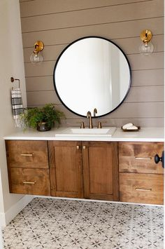 This charming bathroom boasts a brow shiplap wall lit by two brass and clear glass globe sconces mounted on either side of a round black mirror hung over a brown oak washstand.