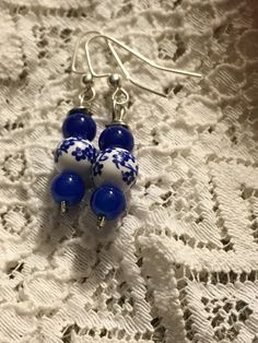 These earrings are made with royal blue glass, and delicately designed white ceramic spheres wrapped in dainty blue flowers. Giving Grannies -fine...