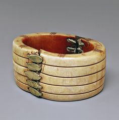 Ethiopia | Old ivory bracelet; large oval form, the exterior with deep parallel grooves, the top and bottom with panels of dotted ornament, the two halves joined with brass rivets,golden patina to the exterior, dark reddish brown patina to the interior. | Est. 1'000 - 1'500€ ~ (Jan '15)