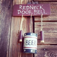 """'Redneck Door Bell' windchime   featuring a red wood sign with white lettering and a black wire hanger, 1 painted metal can strung with jute twine and 2 wood shot gun shell replicas strung with jute twine.  Measurements: 9.75"""" wide x 12.75"""" high"""