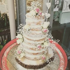 Rustic Naked Wedding Cake. White sponge, white chocolate cream cheese frosting. Pink and white roses, baby breath.