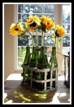 large flowers in wine bottles inside a wine caddy. Gorgeous sunflowers!