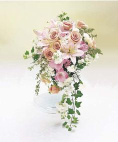 cascade bouquet that is full of peach roses, light pink Oriental lilies, pink gladiolus, white hydrangeas, pink bouvardia, white mini carnations, white stock, ivy, white wax flower and plumosus