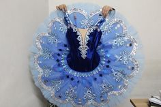 This professional stage costume is suitable for many classical variations and especially for the Blue Bird variation, Princess Florina's variation and Pas de Deux, La Fille du Pharaon, Raymonda, and other variations. The color of this tutu is an exquisite deep blue. The professional, dark blue bodice fastens in the back with a double row of hooks and eyes. The front features a deep V and a nude inset. Embellishments are made using silver trims and sequins, silver appliques, blue diamonds ...