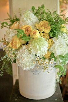 Hydrangea Arrangement, we could replace the yellow/orange roses with juliet garden roses, and include loos greenery, hydrangeas, and some other loose flowers (this contains chamomile, the little daisy looking flowers...we don't have to add that of course.)