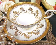 OFFERING THIS PRETTY JUST FANTASTIC TEA CUP AND SAUCER GORGEOUS PIECE , MADE BY FOLEY AND IT IS AN OLDER SET MADE IN THE EARLY 40S AND ALL GOLD GILT SCROLL WORK IN 24KT GOLD AND ALSO YOU HAVE BANDS OF GOLD GILT AS WELL MADE OF A FINE BONE CHINA WITH NO CHIPS AND NO CRACKS AND NO