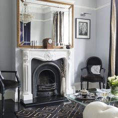 In the living room, a traditional fireplace, antique chandelier and beveled, gold-framed mirror to complement the style and period of the house. Grey walls create a calm backdrop for the monochrome furniture, while gold accents add a sophisticated look