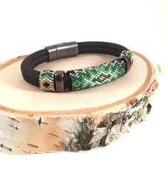 The Green Clover peyote bead woven bangle has an inspiring alluring color of greenery that is around us. The design has 3 shades of green with silver-lined crystal, galvanized gold and matte black glass seed beads. All premium glass beads are by Miyuki, all combined together with a strong gunmetal magnetic clasp and gunmetal spacers to enhance the design. The gunmetal components are lead & nickel free. The band is Portuguese cork wrapped around a solid leather core. All of my patterns are…