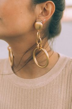 Wear chunky metallic hoops with a muted color palette. Get the look here.