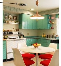 So much to love in this delightful midcentury kitchen, from the original fan, to that fabulous flying saucer pendant light, to the contrasting turquoise cabinets and bright red tulip chairs... very cool.