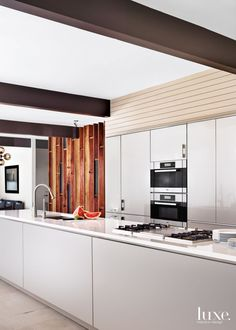 The walnut-and-blackened steel entry wall complements the adjacent painted-shiplap-paneled walls, which outline the kitchen cabinets. A concealed pantry resides along the wall. Painted metal beams overhead add another layer of interest. All of the appliances are by Miele, and the Hansgrohe faucet is from Moore Supply Company.