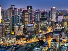 """Osaka city as the sun fades from the Umeda Sky building at sunset.  Notice the tubular-shape building, in the middle right of this image, that has the motorway running through it.   It is the """"Gate Tower Building""""  http://en.wikipedia.org/wiki/Gate_Tower_Building"""