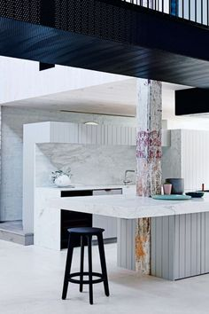 11 of the most beautiful white and neutral kitchens: Marble combines beautifully here with vertical panelling to create a modern and architectural space in this warehouse-style home.