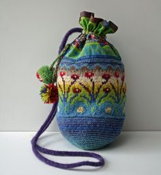 Folk Bag - Sirkka Könönen: crocheting, knitting and cotton print fabric. Inspired by the textile artist Sirkka Könönen's work.     Height: appr. 13 inch  Circumference: appr. 15 inch  : estonian and finnish  wool