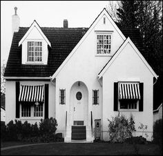 Typical modest American English-style  cottage . . .c.1925 . . .  black and white awnings with white painted brick . . .Architectural plans often ordered through Sears Roebuck Catalog.