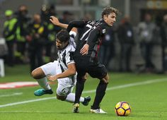 Manuel Locatelli (R) of AC Milan competes for the ball with Sami Khedira (L) of Juventus FC during the Serie A match between AC Milan and Juventus FC at Stadio Giuseppe Meazza on October 22, 2016 in Milan, Italy.