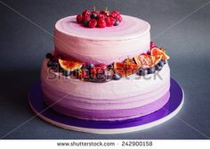 Two tiered purple cream cake with fruit on dark gray background - stock photo