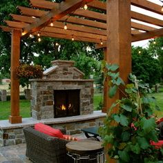 Pergola with string lights, woven outdoor furniture, fireplace insert and sturdy, yet attractive flooring.