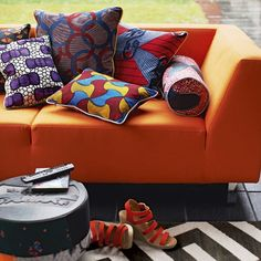 another orange- love the add of color but keep in mind not overloading the senses and trying to use as much LIGHT colors as possible in BULK pieces to lighten the room. such as additional chairs, entertainment center piece possibly more of a light wood with balck accent pieces like the ottoman