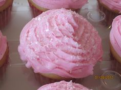 vanilla cupcake with strawberry frosting and clear sugar sprinkles