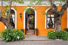 image 8-802-4310 Uruguay, Colonia del Sacramento, Trees and orange facade of historic building in old town