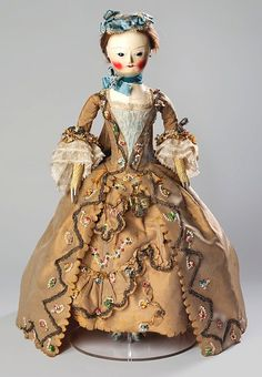V and A: fashion doll with accessories (pandora) c. 1755  Fabulously dressed pandora with cap, necklace, robe, two petticoats, engageants, mitts, stomacher, chemise, corset, under-petticoat, pocket, pincushion, stockings, shoes, fob watch, etui, and wooden box