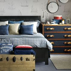 This nautical themed bedroom uses shades of blue and boat wallpaper to create a charming coastal look