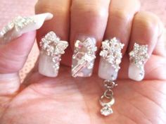 SWAROVSKI CRYSTALS AND A DIAMOND RING DANGLE HANGING FROM A PIERCED NAIL.