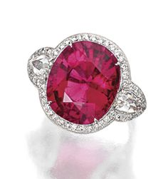 RUBELLITE AND DIAMOND RING.  The cushion-shaped rubellite weighing 14.80 carats, flanked by 2 pear-shaped rose-cut diamonds weighing approximately 1.10 carats, bordered by numerous small round diamonds weighing approximately 2.00 carats, mounted in platinum