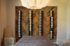 Chic dining room features a white beaded chandelier hanging over a reclaimed wood dining table lined with linen slipper chairs facing a wall niche lined with verticla wine racks lining a wood herringbone wall.