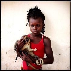 Mariama, 10, and her pet monkey, Bolama, Guinea-Bissau, Nov. 11, 2012. Photo by Holly Pickett. From the Everyday Africa project.