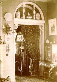 """Late Victorian eclecticism: Queen Anne Revival woodwork meets """"Asian"""" in the form of Moorish and Chinese elements. Portieres, or door curtains, were used to keep heat in the room where the fire was lit; they're usually fabric, but this one looks like some kind of """"oriental"""" rug."""