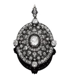 A diamond brooch/pendant, circa 1890 The oval openwork plaque designed as a radiating starburst, set throughout with cushion-shaped diamonds, the largest to the centre, suspended from a detachable similarly-cut diamond-set bale, mounted in silver and gold, principal diamond approx. 1.15cts, remaining diamonds approx. 4.05cts total, length 5.0cm