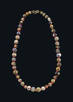 A PHOENICIAN GLASS EYE BEAD NECKLACE CIRCA 6TH-2ND CENTURY B.C. Composed of forty-five globular beads of various sizes, in blue, turquoise, yellow, green and white with compound eyes, and a blue mosaic bead with yellow and red rosettes, restrung with a modern hook and loop closure 20 in. (51 cm.) long