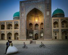 Hernandez Marzal (@hernandezmarzal) photographs a bride and groom at Mir-i-Arab Madrasa across the way from the Kalon Mosque in #Bukhara #Uzbekistan as children ride their bikes in the background. // #tinypeopleinbigplaces #architecture #architecturephotography #goldenhour #magichour #composition #fineartphotography #artphotography