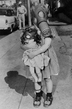little girl wears a gas mask while playing with doll