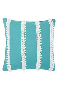Bold bands of tiny pompoms lend festive flair to a vibrant cotton pillow plumped with lush feathers.