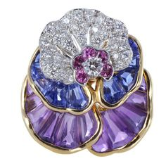 Oscar Heyman Brothers pansy pin in Platinum and 18 karat yellow gold consisting of 38 round brilliant cut diamonds weighing 1.23 carats, 9 sapphires weighing 4.90 carats, 11 amethysts weighing 4.78 carats and 5 purple sapphires weighing .44 carats.