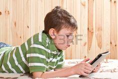 Teenager Junge auf dem Bett liegend mit einem Tablet PC Stockfoto