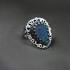 Proved, strongly expanded ring made  scratch by hand with silver. Front lace in the form of tears, in which the central point of attracting the attention of agate druzzy shimmering holographic colors of blue, indigo, violet and green. The color depends on the angle of incidence of the light. Its a real stone chameleon. Ring decorated on the sides, back smooth. Silver burnished and polished to shine. Dimensions trim part of the ring is approximately 25x20 mm, dimensions of the stone is…