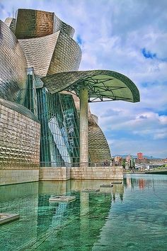 """Guggenheim Museum, Bilbao, Spain, by Frank Gehry – With """"sails"""" of titanium billowing around massive blocks of limestone, what architect Philip Johnson hailed as """"the greatest building of our time"""" seems destined to voyage across the Nervión River. Interesting Buildings, Amazing Buildings, Museu Guggenheim Bilbao, Places Around The World, Around The Worlds, Architecture Unique, Madrid, Wonders Of The World, Beautiful Places"""