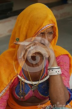 Portrait of rural woman in traditional cloths and jewellery pointing finger, Rajasthan, India