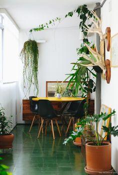 Mesa de jantar redonda revestida com fórmica amarela e piso de ladrilho hidráulico verde.
